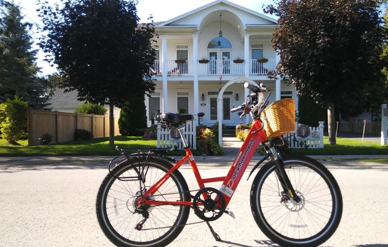 An e-bike in front of a colonial style white house.