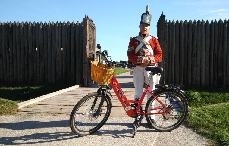 A costume soldier stands behind an e-bike at Fort George.